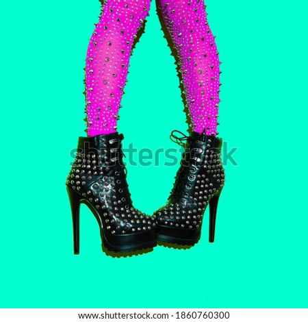 Fashion legs in heel party boots on green minimal background. Stylish clubbing look. Minimal art