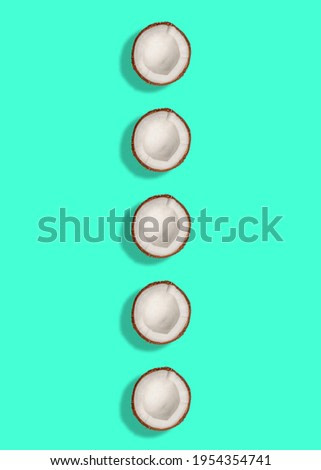 Ripe half of coconuts on green background. Flat lay, top view. Summer concept.