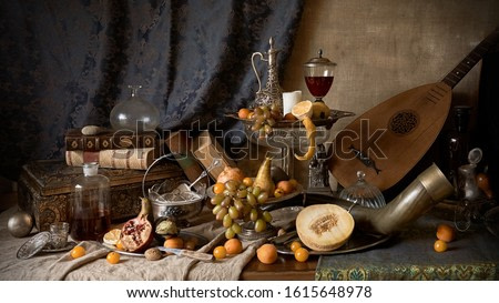 Still life in old masters style with hunting horn, wine, silver dishes, fruits, guitar lute, apricots and grapes.