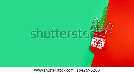 Flat lay photo with Christmas decorations on geometric red and green background. Christmas Red Knitted Mittens with Snowflake Motives. New Year concept with copy space. Long wide banner