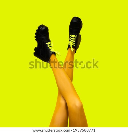 New gray female boots on long slender crossed woman legs in bright yellow tights isolated on yellow background. Pop art concept with Heavy female Boots