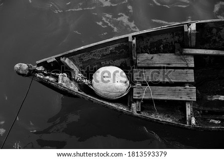 Close up of front side of small fisherman wooden boat moored in port. small row boat floating , view from top angle black and white photography