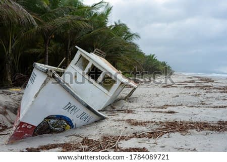 Wrecked boat on a beach in the Caribbean Sea in Colombia