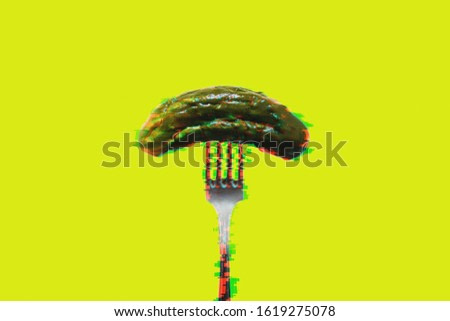 Pickled cucumber on a fork on a yellow background in glitch effect