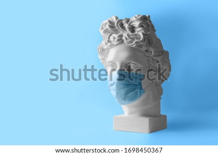 White plaster statue of the head of Apollo Belvedere in a medical protective mask. The concept Museum is closed for quarantine.