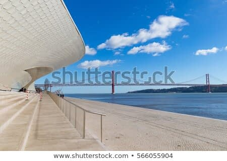 Facade of the new art, technologies and architecture museum in Lisbon. The 25 April bridge over the tagus river