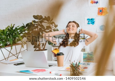 selective focus of happy girl in headphones stretching while sitting at desk near laptop, disposable cup and paintings