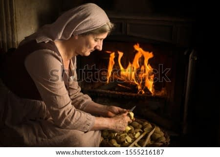 Renaissance old master portrait of a peasant woman peeling potatoes at her fireplace