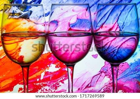 Three wine glasses in a row with colorful light painting behind, Set of three wine glasses with red, white and rose wine, banner, alcohol drinks
