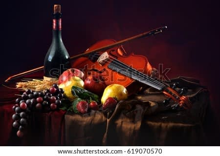 Violin with a bow on a red background next to a bottle of old wine and wet fruit.