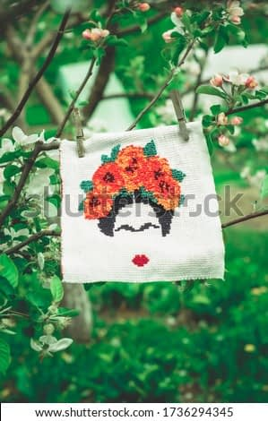 An embroidery depicting Frida Kahlo dries in the wind, attached with clothespins, in the garden.