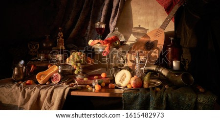 Still life in old masters style with lobster, glass of wine, silver dishes, fruits, guitar lute and hunting horn.