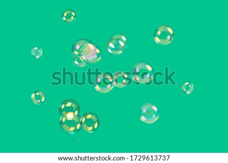 Soap bubbles isolated on a green background. Copy space.
