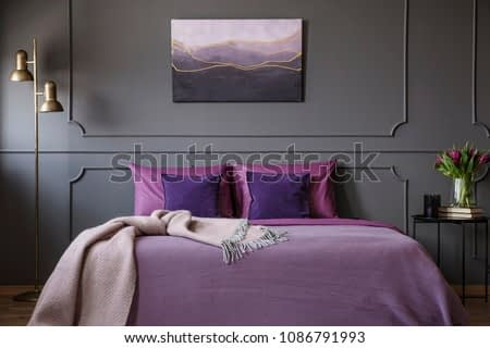 Pink blanket on violet bed in elegant bedroom interior with painting on grey wall with molding