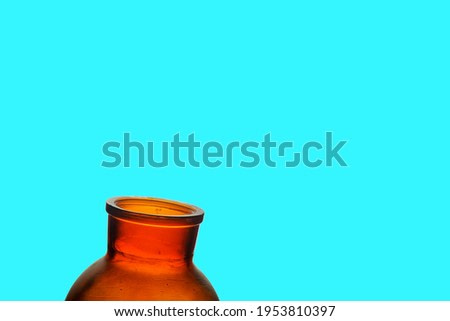Dusty open jar on bright aqua blue background. Red brown jar on blue.