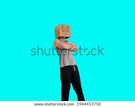 A man stands with a silly box on his head with a blue background