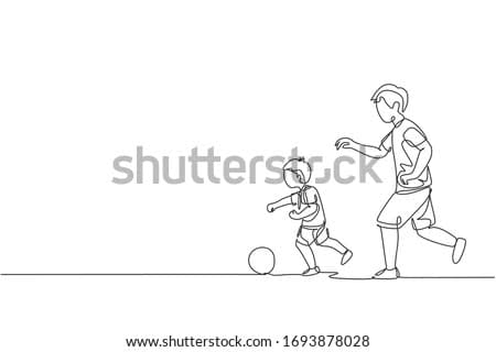 One single line drawing young dad running and playing football soccer with his son in public field park vector graphic illustration. Happy family parenting concept. Modern continuous line draw design