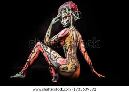close up portrait of young graceful nude girl with professional bright colorful body painting. beautiful expressive  woman with many pigtails. pop art
