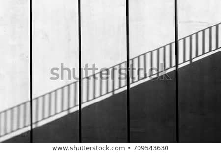 Sunshine on wall. Abstract art and design. Shadow texture.Thin lines of light on the wall. Space for text. Abstract modern architecture. Light and shadow on gray wall.