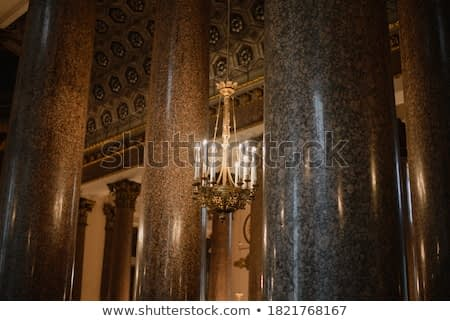 in the church building, among the columns, a candlestick with burning candles weighs