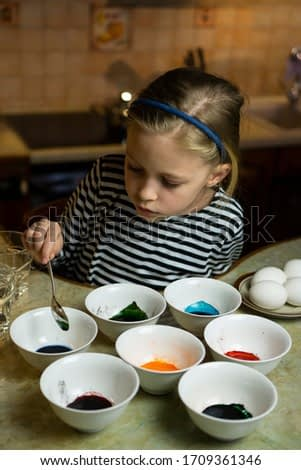 Caucasian blond child girl in a striped dress painting Easter eggs sitting at cosy wooden home kitchen table with many white plates bowls with paint. Arts and crafts at home easter concept