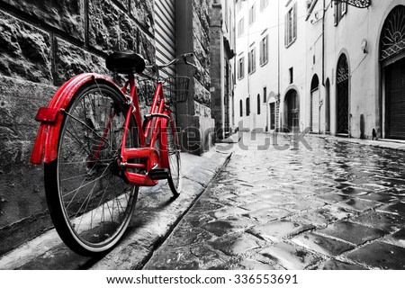 Retro vintage red bike on cobblestone street in the old town. Color in black and white. Old charming bicycle concept.
