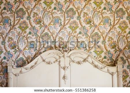 Antique floral french wall paper with ornate decorated wooden headboard