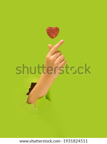 K pop concept. A girl hand showing fingers heart gesture. Red glittery heart above. Bright green in background.