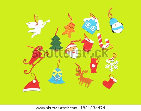 Concept of craft homemade felt Christmas tree toys on a colored background. Green set.