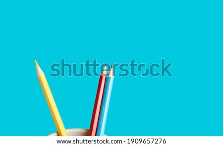 colored pencils in a stand on a blue background