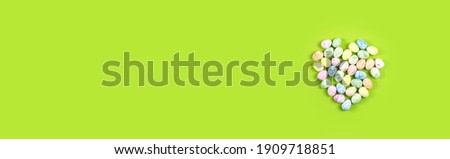 Flat lay composition of Happy Easter holiday concept. Colorful heart from little pastel eggs on green background. top view, banner, copyspace