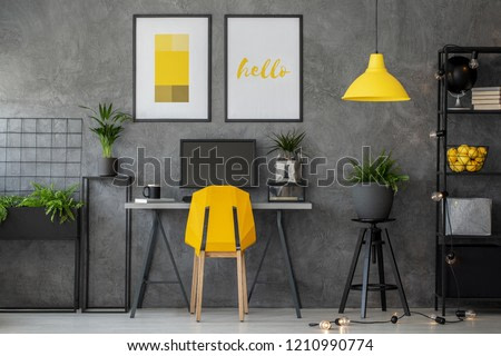 Stylish yellow and grey home office with industrial furniture and urban jungle, real photo with posters on concrete wall