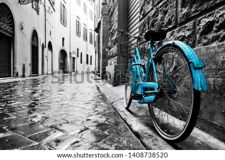 Retro blue bike on old town street. Color against black and white. Vintage style. Florence, Italy
