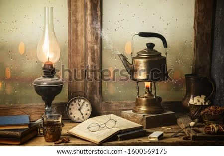 Classic still life with hot tea pot placed with illuminated vintage lamp, old books, cup of tea on rustic wooden table.
