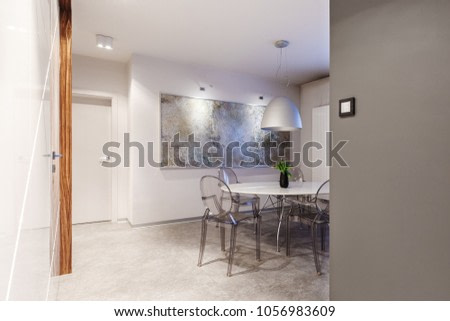 Modern apartment interior with a small, cozy dining room with white and gray walls, a round table, modern, transparent chairs, low hanging ceiling lamp and a large painting art