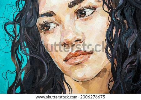 Fragment of work where fiery black curly hair as a waterfall falls from the head of a white-faced girl. .Portrait of a Hispanic woman on a blue background. Oil painting on canvas.