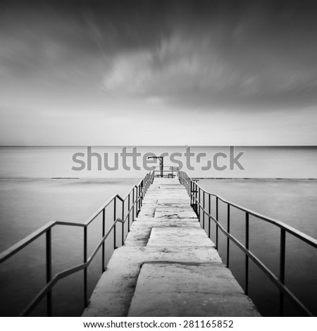 beautiful minimalist black and white seascape with sea wave cutter and milk water. shot taken in daytime with long exposure