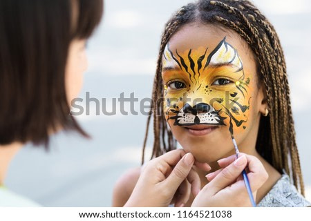 Cute little tiger. African-american girl getting face painting outdoors, having fun, copy space