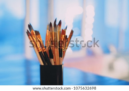 Assorted dirty painting brushes in glass flask. blue background