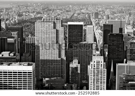 Black and White photograph of Midtown Manhattan with a view of Central Park and Upper Manhattan further back. Aerial view of Manhattan's skyscrapers and buildings, New York City.