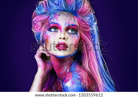 close up  portrait of young beautiful girl with colorful face painting. Halloween professional makeup. hair in paint. beauty portrait. blue and pink hair