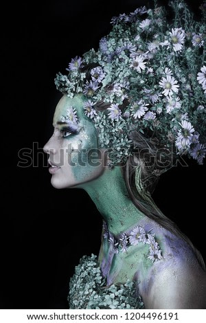 close up portrait of young beautiful girl with flower professional makeup. elf princess with flowers in hairstyle.  Halloween makeup. bright face art. spring fairy of flowers. flowers on face