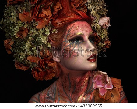 close up portrait of young beautiful girl with flower professional makeup. elf princess with flower crown on head.  Halloween makeup. bright face art. spring fairy of flowers. orange hair