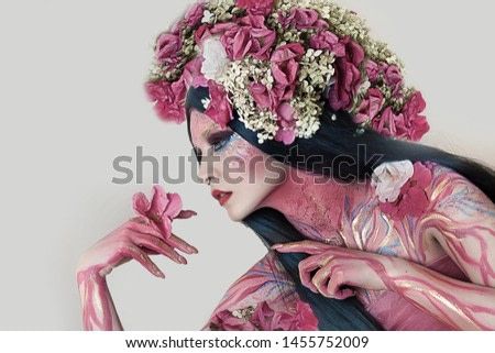 close up portrait of young beautiful girl with flower professional makeup. elf princess with flower crown on head.  Halloween makeup. bright face art. spring fairy of flowers. black lush hairdo