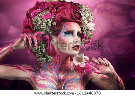 close up portrait of young beautiful girl with flower professional makeup. elf princess with flower crown on head.  Halloween makeup. bright face art. spring fairy of flowers. pink hair