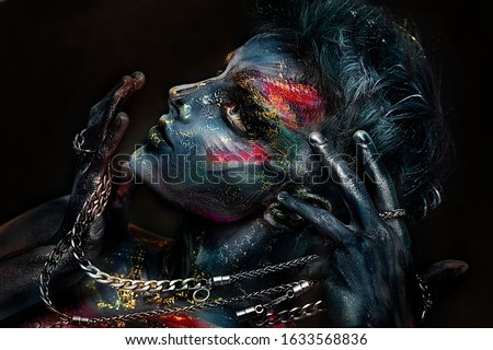 close up conceptual portrait of man with colorful face painting. emotional guy. face in paint. chain in hands