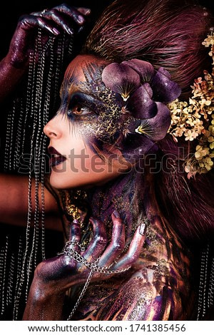 close up portrait of young beautiful girl with Halloween professional makeup. elf princess with flower crown on head. bright face art. spring fairy of flowers with chain
