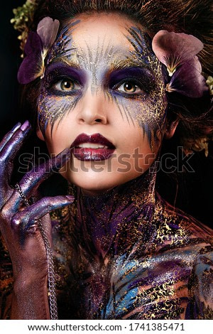 close up portrait of young beautiful girl with Halloween professional makeup. elf princess with flower crown on head. bright face art. spring fairy of flowers
