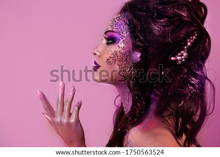 close up  portrait of young beautiful girl with colorful face painting. Halloween professional makeup. hair in paint. beauty portrait. colorful beads on face. profile