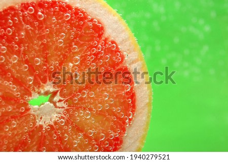 Slice of grapefruit in sparkling water on green background, closeup with space for text. Citrus soda
